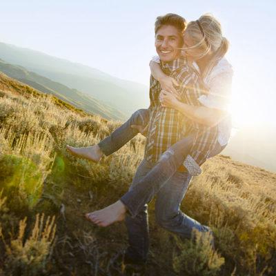 Couple playfully piggybacking through field.